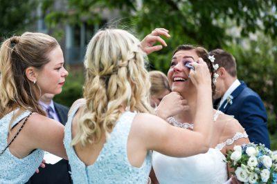 Hochzeitsgast wischt Braut die Tränen aus dem Auge